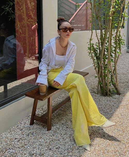 Yến Trang tranh thủ chụp hình khi ghé mua cafe. Nữ ca sĩ chào thu cùng set đồ tông vàng - trắng bắt mắt, điểm nhấn là chiếc quần ống loe màu rực.