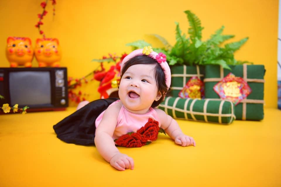 Từ bé xíu, em đã thích nghe mọi người nói chuyện và lanh lẹ. Cô bé cười tươi khi được diện áo dài để chụp ảnh dịp Tết Nguyên đán.