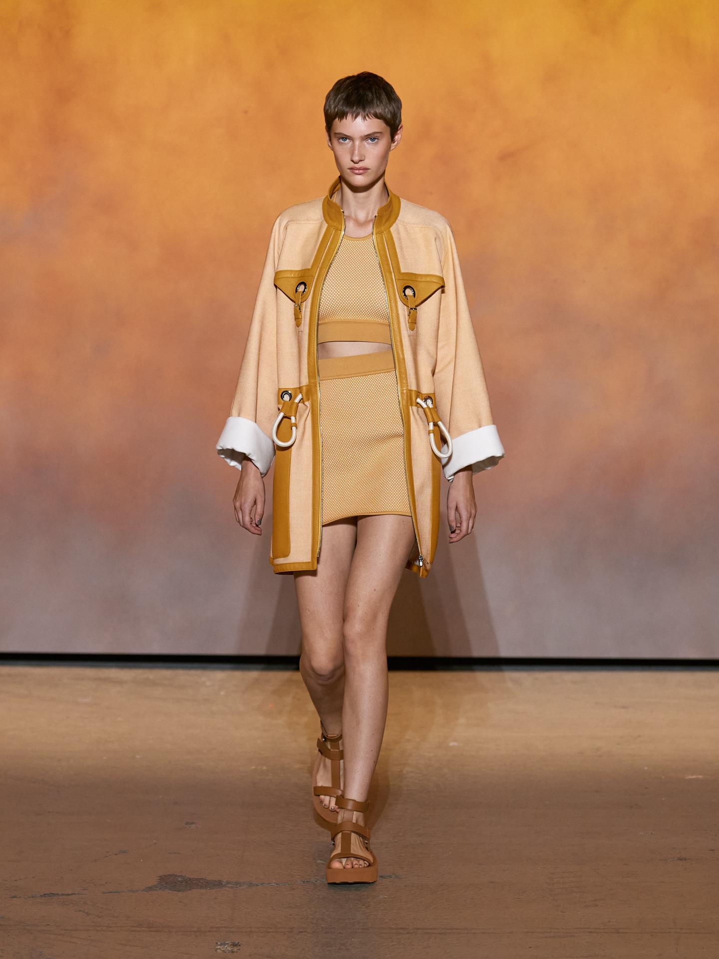 Khoen của dòng túi Mangeoire và chất liệu da cừu được lồng ghép trên áo khoác. Mini skirt và crop-top ứng dụng kỹ thuật đan lưới 3D, đồng điệu với tổng thể trang phục.