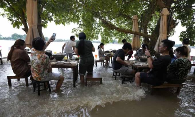 Khách hàng tranh thủ dùng điện thoại ghi lại trải nghiệm thú vị khi ngồi ăn trong nước lũ. Ảnh: AP