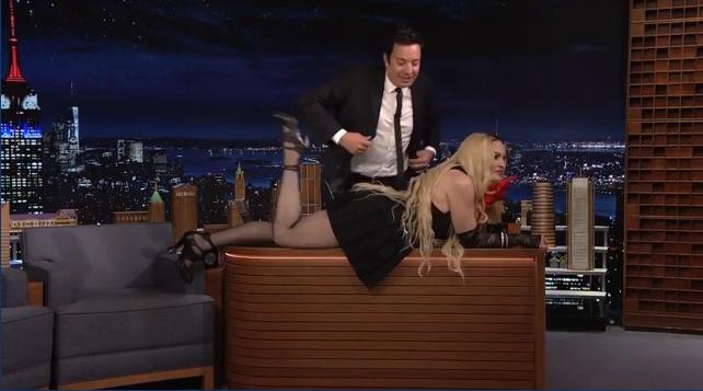Madonna trèo lên bàn tạo dáng. Ảnh: YouTube