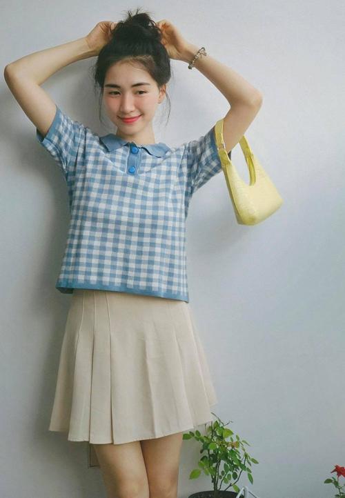 Công thức áo polo cắm thùng cùng chân váy xếp ly được Hòa Minzy yêu thích gần đây để có diện mạo xinh yêu tựa nữ sinh. Chỉ với 195.000 đồng, người đẹp sắm được mẫu áo dệt kim kẻ caro xanh, phối hòa hợp cùng chân váy màu be 155.000 đồng.