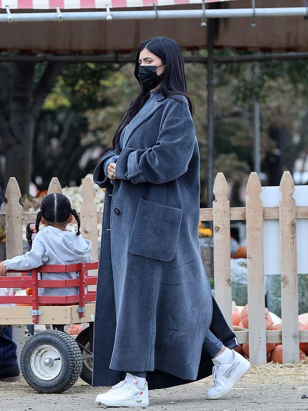 Bà bầu đeo khẩu trang tránh dịch và mặc đồ kín mít. Cô diện bodysuit màu xám và áo khoác rộng ton sur ton.