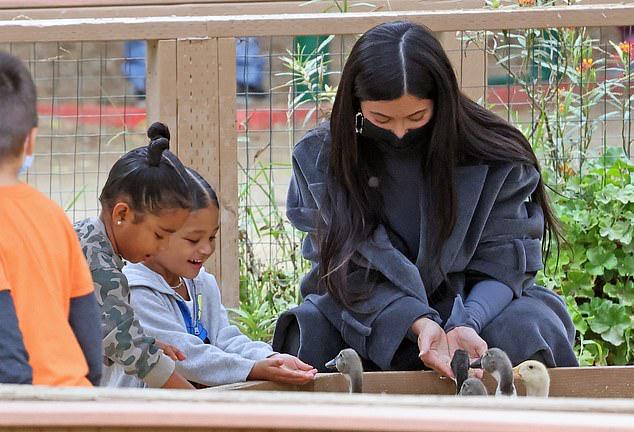 Con gái Kylie (ngồi giữa) và cháu gái thích thú chơi với những con vật ở trang trại.