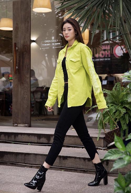 Sơ mi vải kaki màu nổi bật sẽ tạo nên điểm nhấn cho một cây đen gồm áo crop-top, quần skinny và bốt cổ thấp.