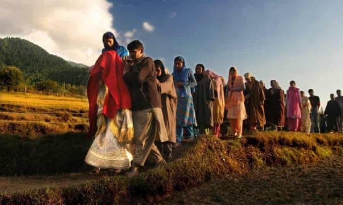 Một cô dâu Kashmir trùm khăn choàng đỏ, cùng với cha mẹ và bạn bè đi đến nhà chú rể để chuẩn bị cử hành đám cưới. Ảnh: EPA