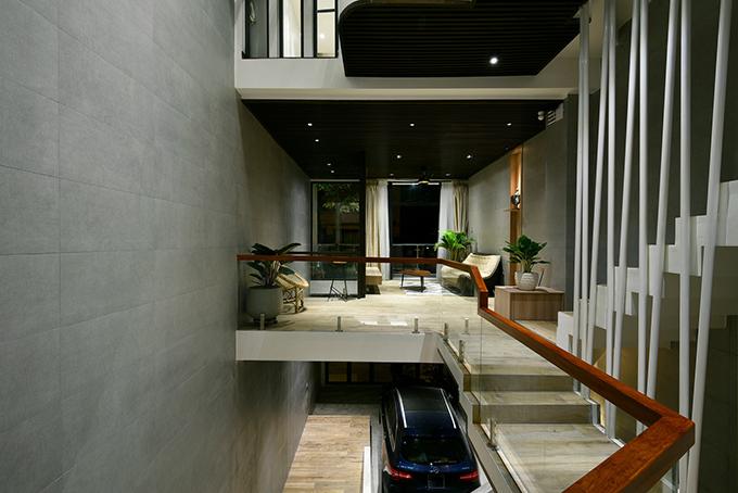 Tầng trệt kiêm gara để xe. Các tầng trên đều có lan can kính giúp không gian rộng rãi so với thực tế và chừa diện tích lớn cho khoảng thông tầng, giúp nhà thoáng, mọi người dễ kết nối.