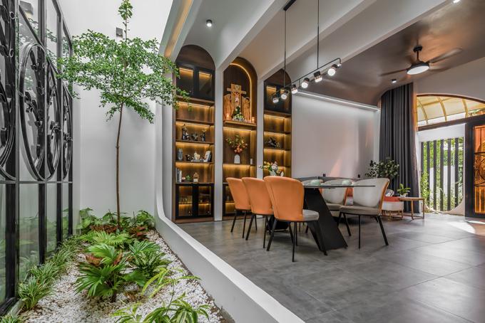 Bộ bàn ghế ở khu vực ăn uống đồng màu với sofa, tạo sự đồng bộ. Bên trên là đèn thả trần. Ngay bên cạnh là giếng trời với các tiểu cảnh, giúp nhà đón nắng tự nhiên, thoáng đãng.