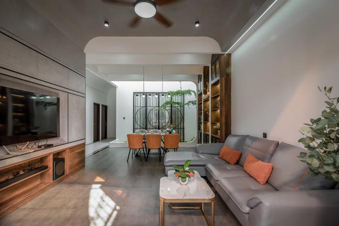 Phòng khách có bộ ghế sofa xám, sát bên là hệ tủ lớn dạng vòm. Bên trong hệ tủ được bố trí hệ thống đèn led, giúp tạo điểm nhấn và tiện nghi trong sinh hoạt.