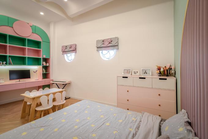 Phòng ngủ của bé gái mang tông hồng, xanh. Phòng được bố trí đầy đủ ánh sáng cũng như hệ cửa sổ. Bố mẹ bé muốn không gian thật tiện nghi để con gái rèn luyện cách sống độc lập, phát huy được ưu điểm, sở thích của bản thân.