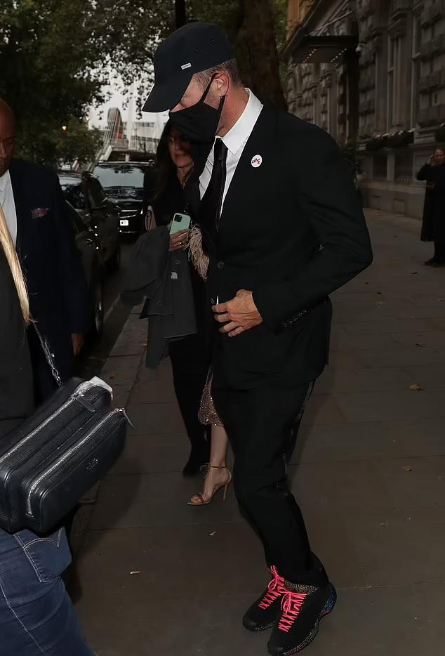 Thủ lĩnh nhóm nhạc Coldplay đeo khẩu trang, đội mũ lưỡi trai kín mít. Anh mặc tuxdeo kết hợp với giày thể thao màu sắc trẻ trung.